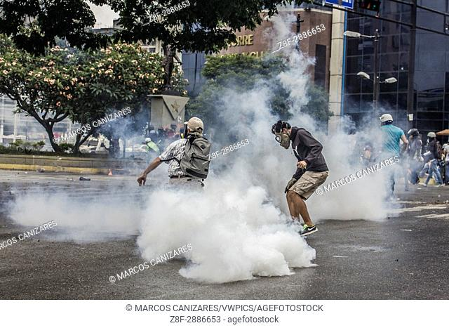 Elderly protester returning tear gas without gloves. An anti-government demonstrator is carried to safety during clashes with authorities in Caracas, Venezuela