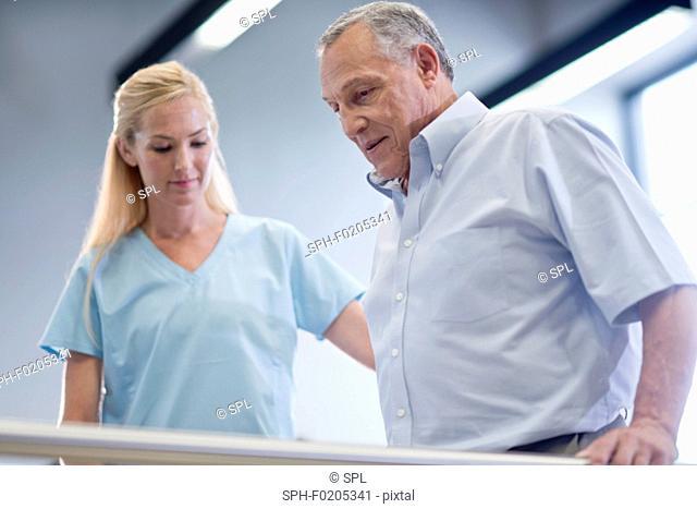 Nurse helping senior man use parallel walking bars
