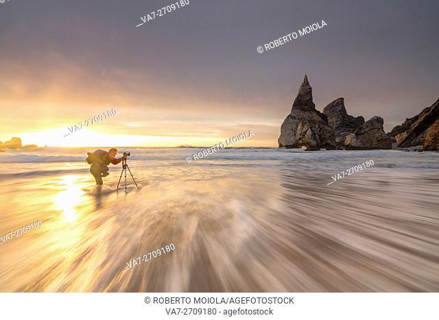 Photographer among the ocean waves under the golden sky at sunset Praia da Ursa Cabo da Roca Colares Sintra Portugal Europe