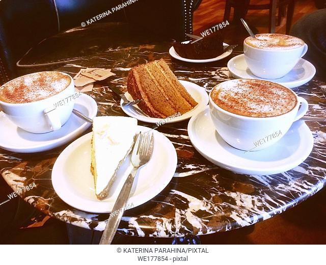 Three cups of Cappuccino and three cakes on the table