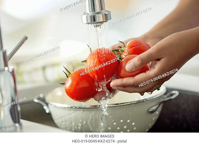 Mid-adult woman rinsing tomatoes in sink with colander