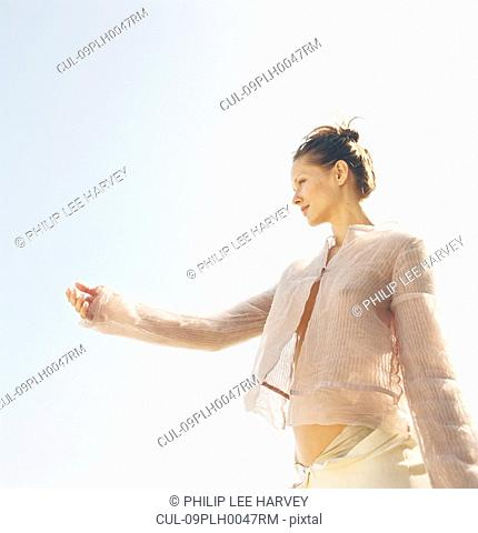 Woman holding out hand on clear day
