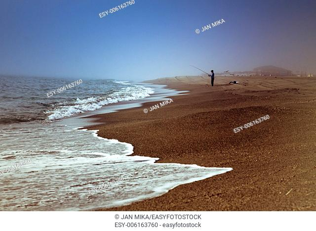 Abstract photo of peaceful colorful beach and silhouette of fisherman
