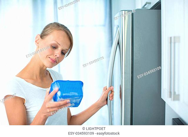 Is this still fine? Pretty, young woman in her kitchen by the fridge, looking at the expiry date of a product she took from her fridge -