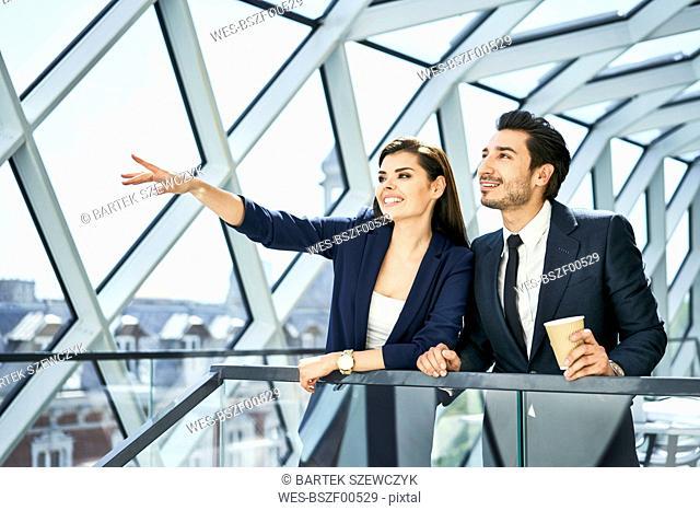 Businesswoman and businessman talking in modern office