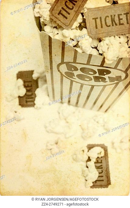 Antique films concept on old movie stubs and pop corn over textured background. Retro movies