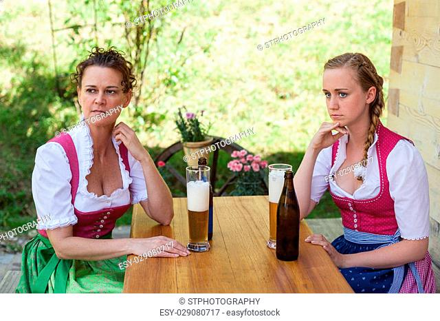 Mother and daughter sitting on a mountain pasture in the Bavarian dirndl festive at a table and have a glass of beer poured