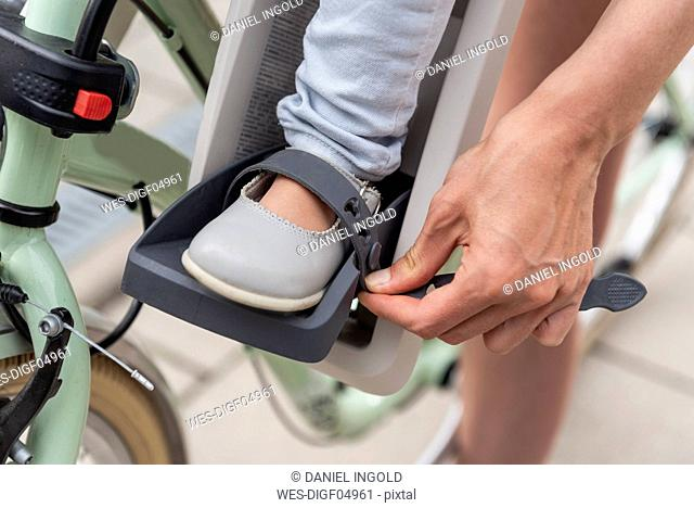 Child sitting in children's seat, mother fastening safety belt