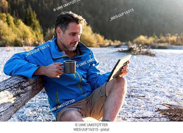 Mature man camping at riverside, using tablet