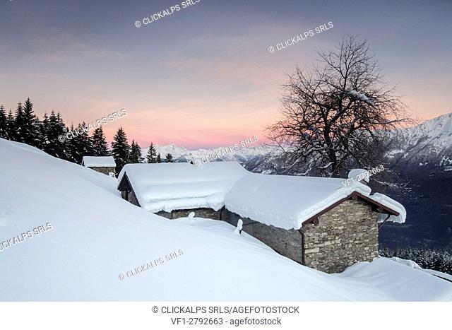 Pink sky at dawn above snow covered huts Tagliate Di Sopra Gerola Valley Valtellina Orobie Alps Lombardy Italy Europe
