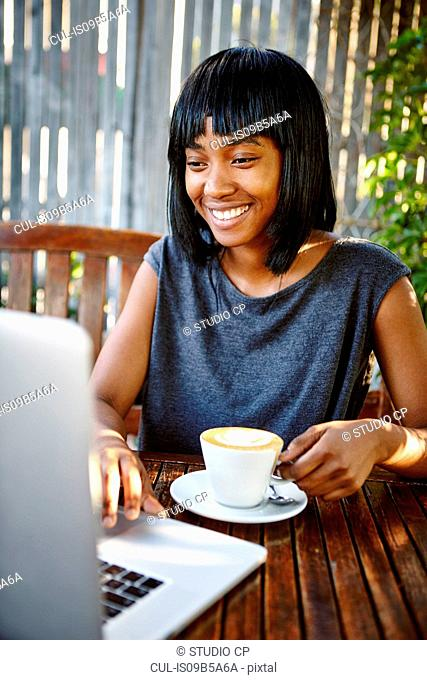 Young woman sitting outdoors, using laptop, drinking coffee