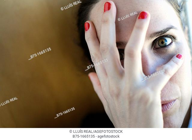 Young woman covering her face with her hands