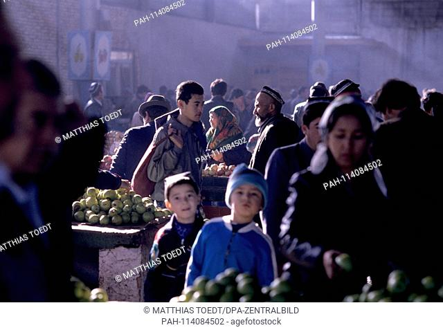 Sunbeams illuminate in the market in Khiva the fruit and vegetables offered for sale, analogous undated image of October 1992