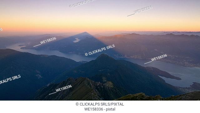 The shadow, with a pyramid form, of Legnone mount over Como lake, Lombardy, Italy