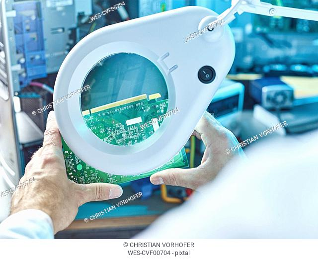 Technician checking circuit board with magnifier