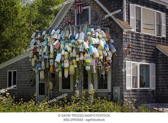 Old lobster bouys hang on a house in Spruce Head, Maine