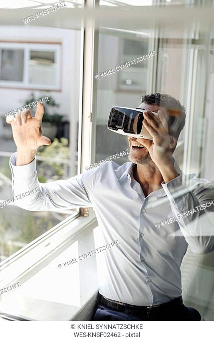 Businessman at the window wearing VR glasses