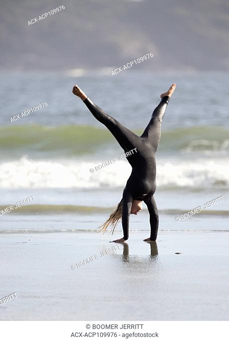 A female surfer shows off her gymnastic skills while on Chesterman Beach, Tofino, Vancouver Island, British Columbia, Canada