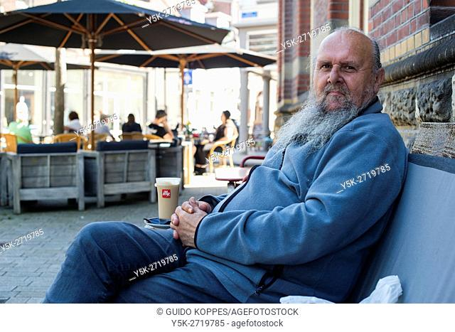 Tilburg, Netherlands. Senior adult male relaxing on a bench surrounded by cafe terrace