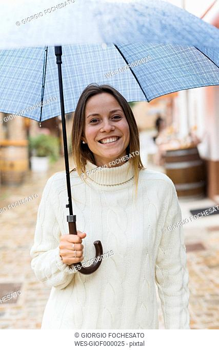 Italy, San Gimignano, portrait of smiling young woman with umbrella