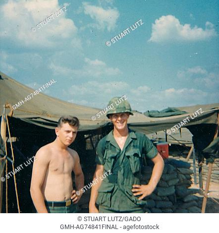 Two United States Army soldiers posing for a photograph while stationed in Vietnam, the soldier on the left is not wearing a shirt and the soldier on the right...
