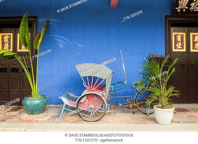 bicycle rickshaw in front of the Cheong Fatt Tze Chinese Mansion in Georgetown, Malaysia