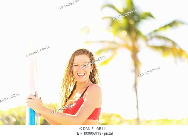 Portrait of young woman holding surfboard on beach