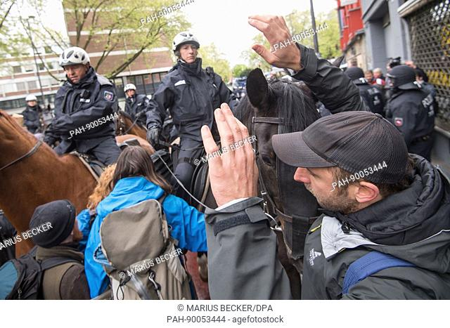 Mounted police ride through crowds of protestors during demonstrations against the Alternative for Germany (AfD) party convention in Cologne, Germany