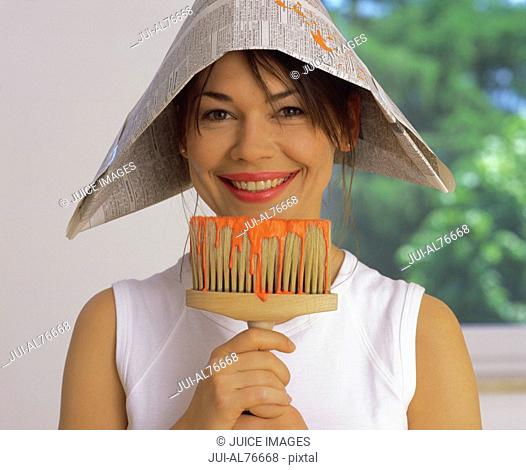 Portrait of a young woman in a newspaper hat holding a paintbrush