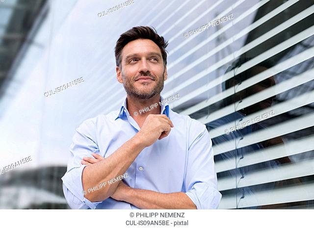 Portrait of mature businessman outside office building