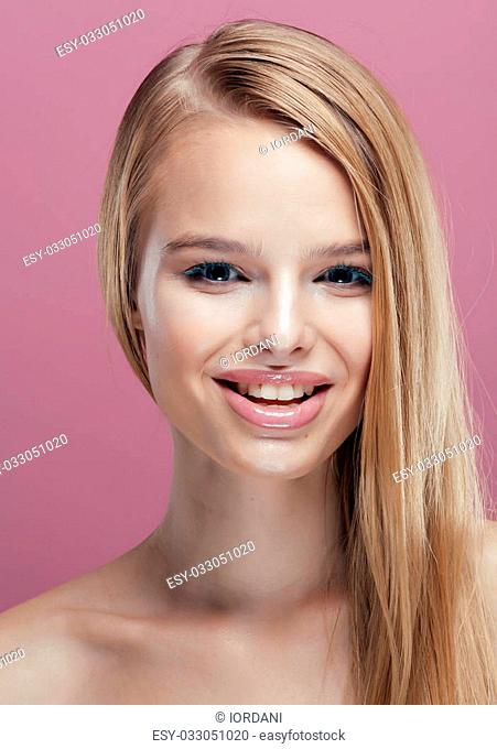 young pretty blonde real woman with hairstyle close up and makeup on pink background smiling