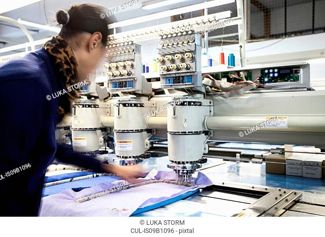 Female factory worker preparing cloth for speed stitching programmed embroidery machine in clothing factory