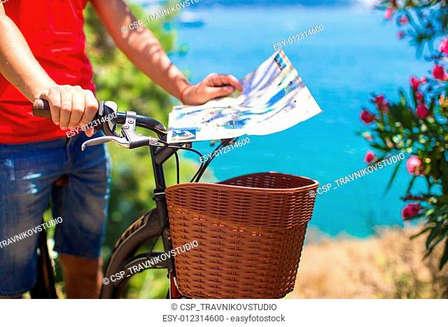 Young traveling man with map of the island bicycling