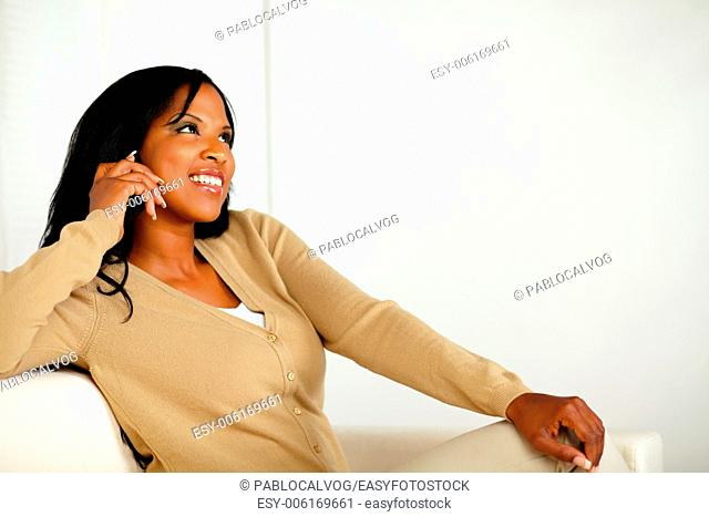 Portrait of a friendly young woman looking up with cellphone while sitting on couch at home indoor