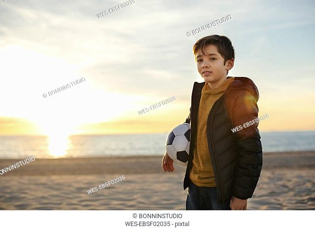 Portrait of boy holding football on the beach at sunset