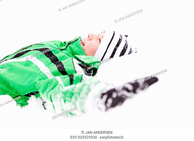 Young child relaxing lying on the fresh white winter snow looking up into the air with a happy grin of enjoyment, upper body profile view in warm winter...