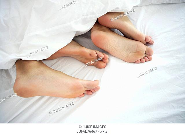 Detail view of a young couples bare feet in bed