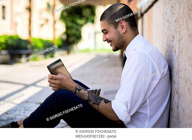 Smiling young businessman sitting on the ground looking at his tablet