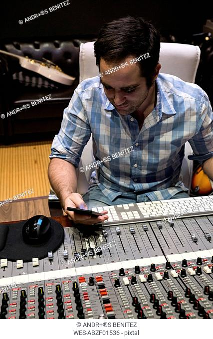 Man in the control room of a recording studio looking at cell phone