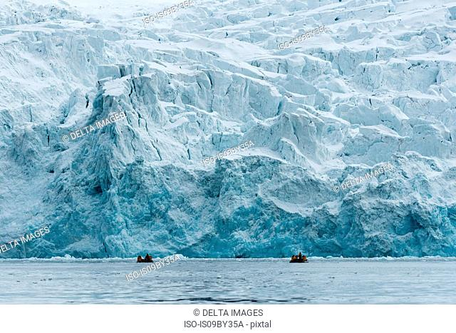 Tourists on inflatable boats exploring Polar Ice cap, north of Spitsbergen, Norway