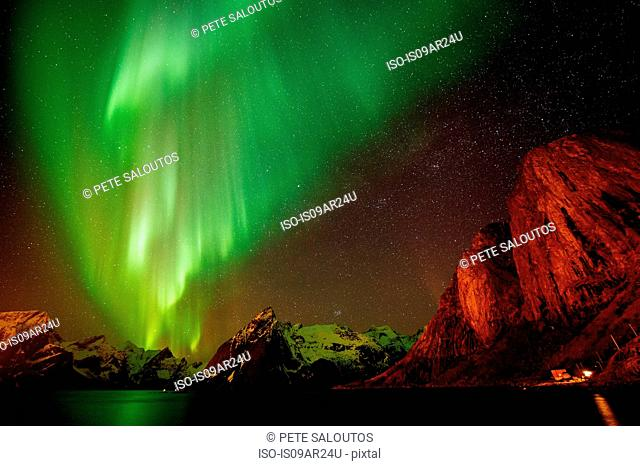 View of aurora borealis over sea and snow capped mountains, Reine, Norway