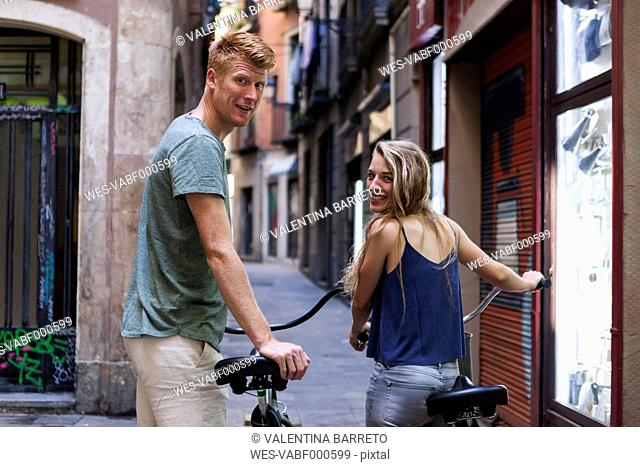 Spain, Barcelona, couple with bicycles in front of an alley
