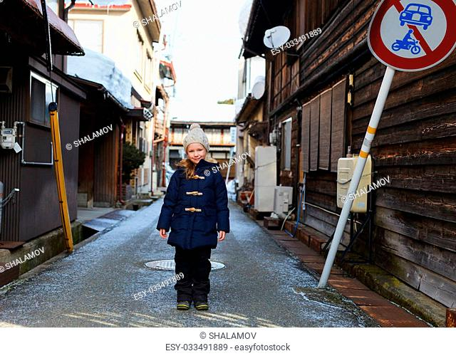 Little girl at old district of historical Takayama town in Japan on winter day