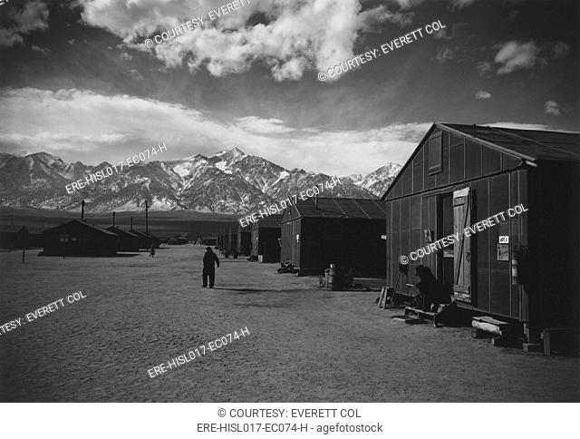 Manzanar Relocation Center, a World War II internment camp for Japanese Americans. A lone man walks on a barracks lined street in the winter of 1943