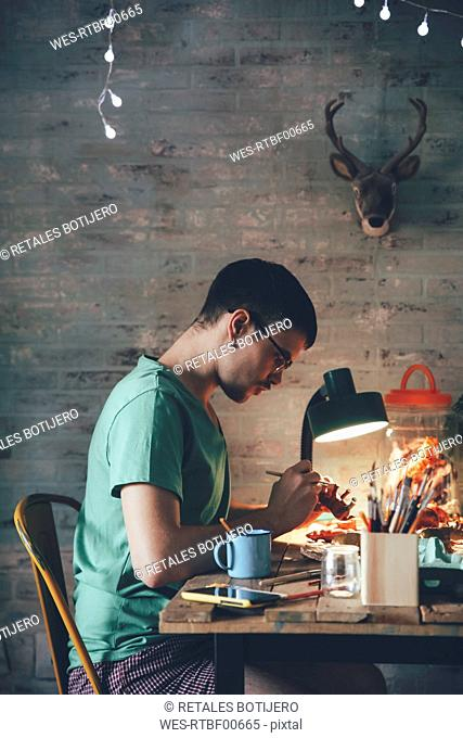 Young man painting animal figurine with paint