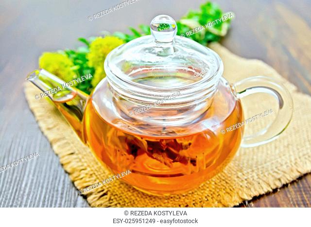 Herbal tea in a glass teapot from the root of Rhodiola rosea on a napkin of burlap, fresh flowers Rhodiola rosea on the background of wooden boards