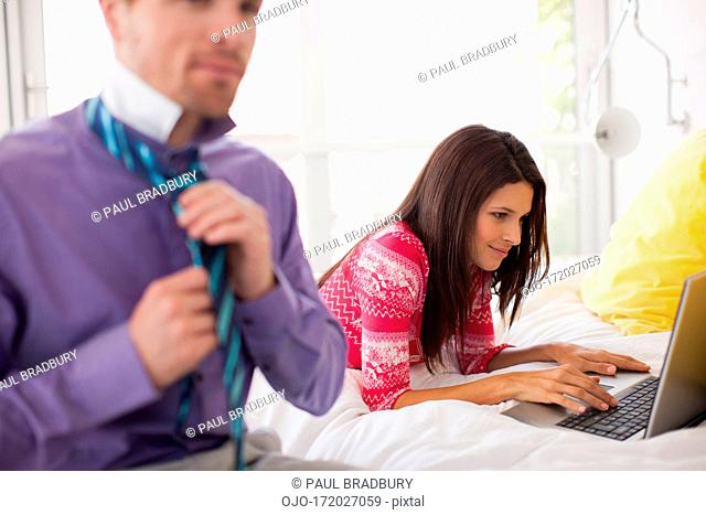 Woman laying on bed using laptop with husband in foreground