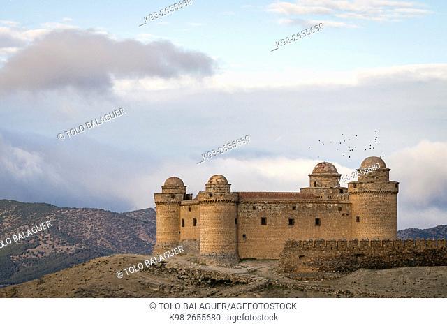 Spain, Andalusia, Granada province, La Calahorra, Flock of birds flying over La Calahorra Castle
