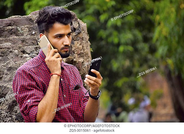 Young man with checked shirt looking at cell phone, Pune, Maharashtra