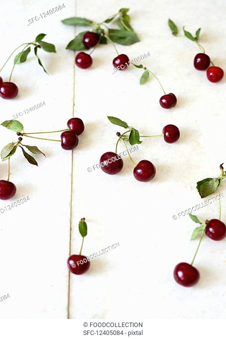 Cherries with leaves on a white surface